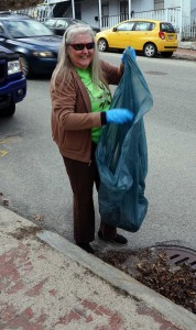 Jacqui Deveneau stuffs litter in the city provided trash bag on Parkside Clean-up Day.