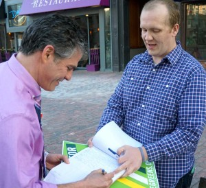 Former State Senator Ethan Strimling signs Tom MacMillan's petition for a $15 minimum wage.