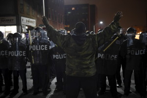 A demonstrator raises his arms as he faces law enforcement officers near Baltimore Police Department Western District during a protest against the death of Freddie Gray in police custody, in Baltimore