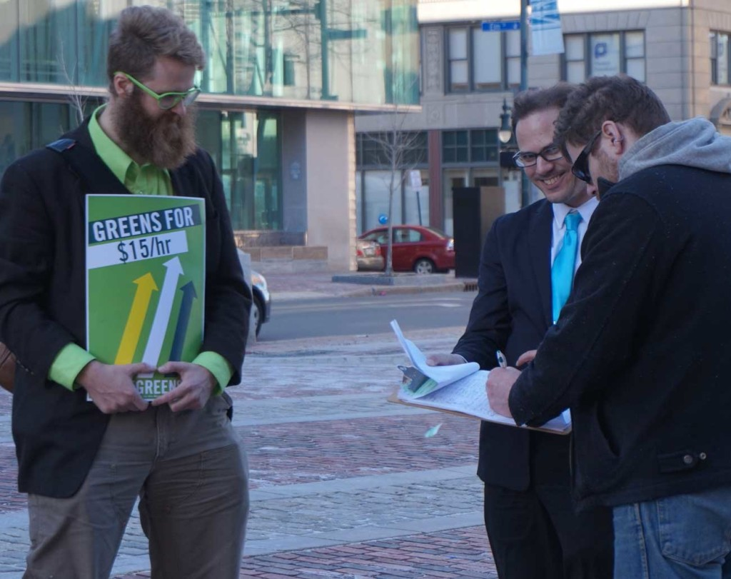 Asher Platts and Adam Marletta collect a signature for the $15 minimum wage referendum petition.