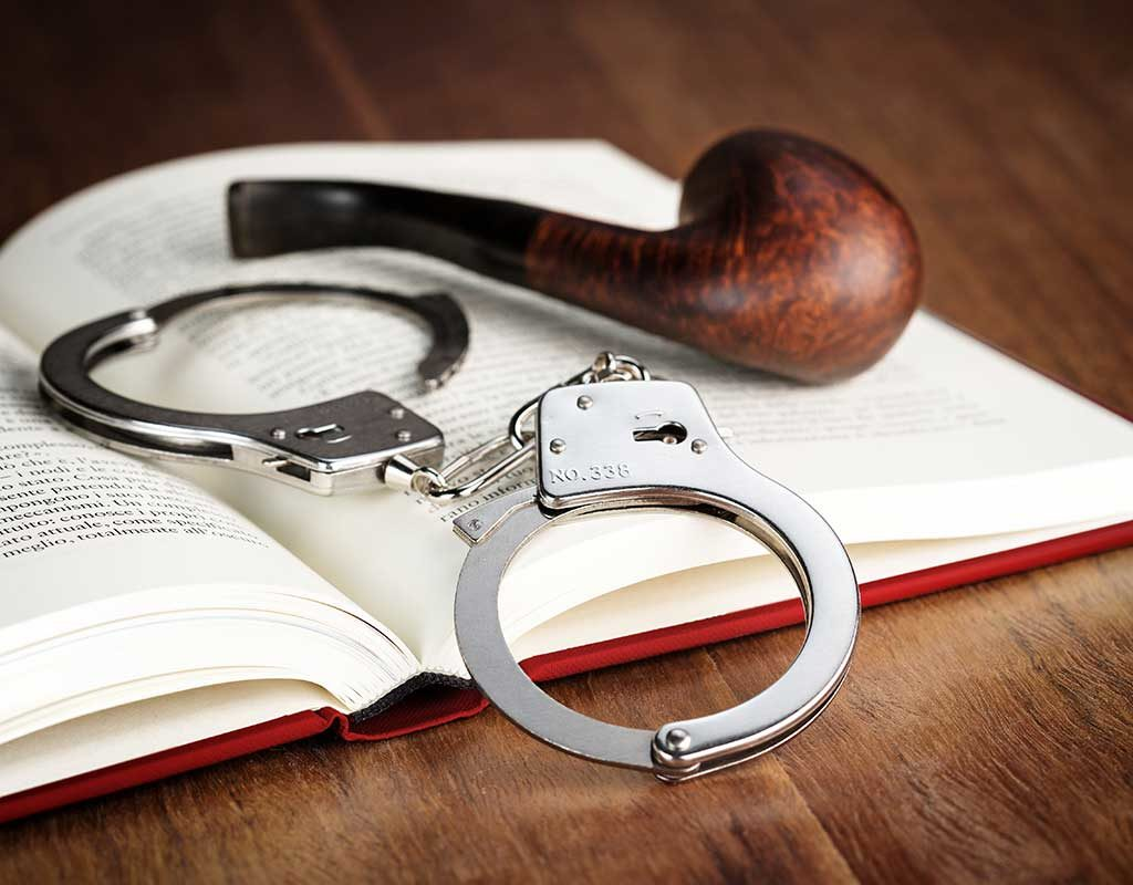 West End News - Book Nook Mysteries - Mystery book with pipe and handcuffs