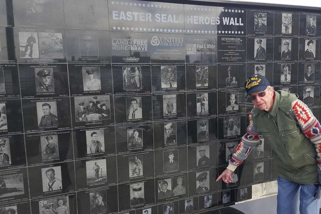 West End News - Veterans Count - Vet at wall pointing at own photo. -Courtesy of Easter Seals.