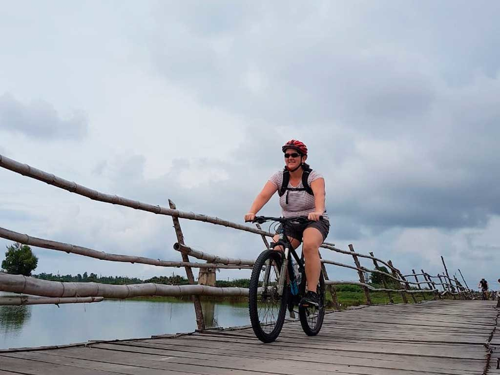 Mary Powers on rickety bridge during bicycle excursion outside of Hoi An