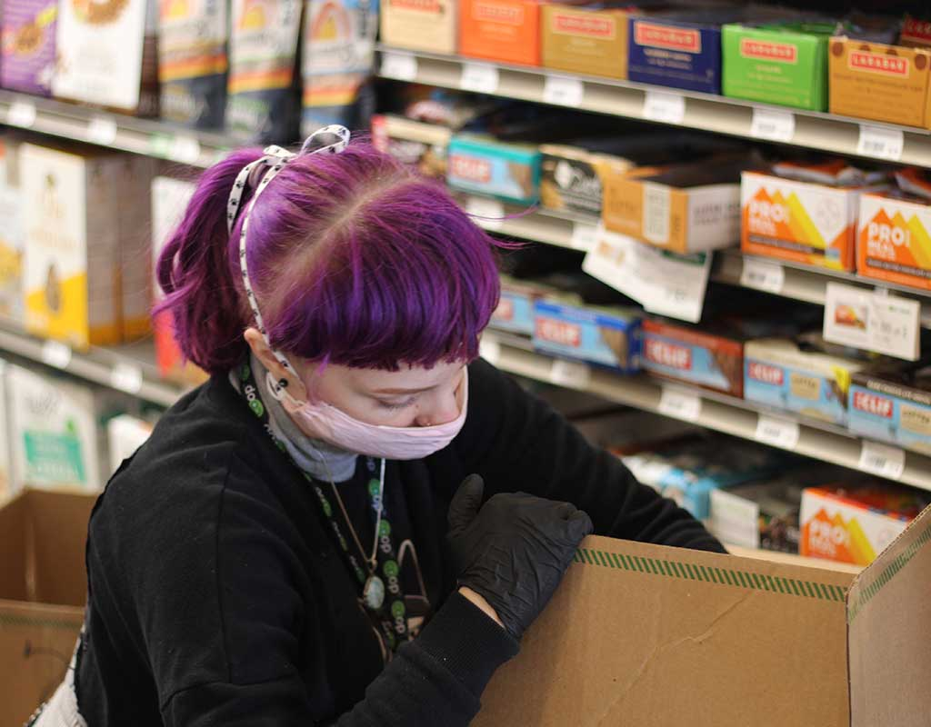 West End News - Local Farms innovate - Haley unpacks a shipment at the Portland Food Co-op