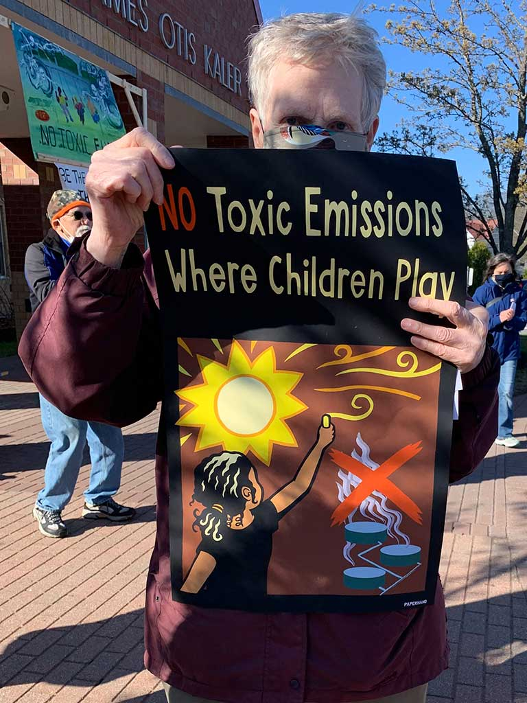 West End News - Battle for Clear Skies - Rachel Burger holding 'No Toxic Emissions' sign - By Karen Silverman, 2021